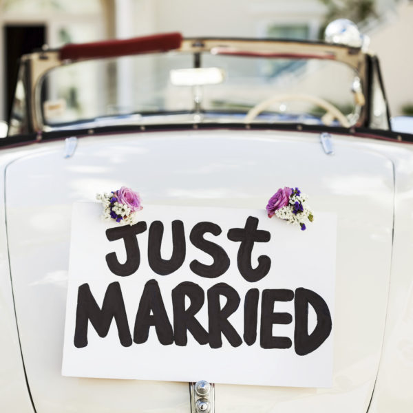 """Close-up of """"Just Married"""" sign attached on convertible car's trunk. Horizontal shot."""